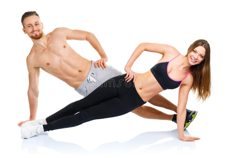 Athletic attractive couple - man and woman doing fitness exercises on the white royalty free stock image