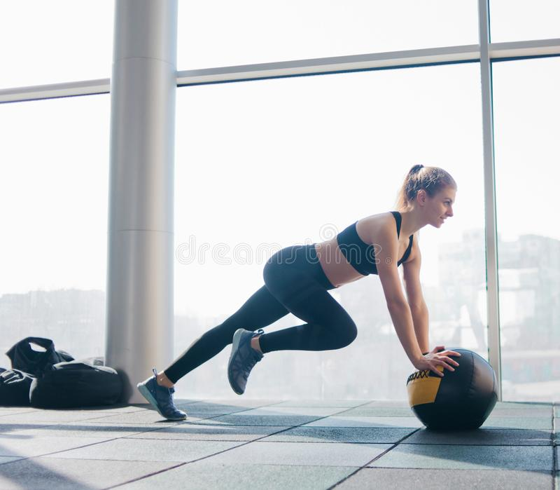 Sport. Athletic attractive woman doing exercise lifting the leg up leaning on the medicine ball against the background of large panoramic window in the gym stock image
