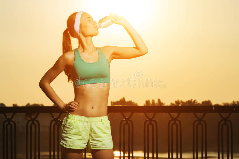 Athletic beautiful sports woman is drinking pure water from the stock photo