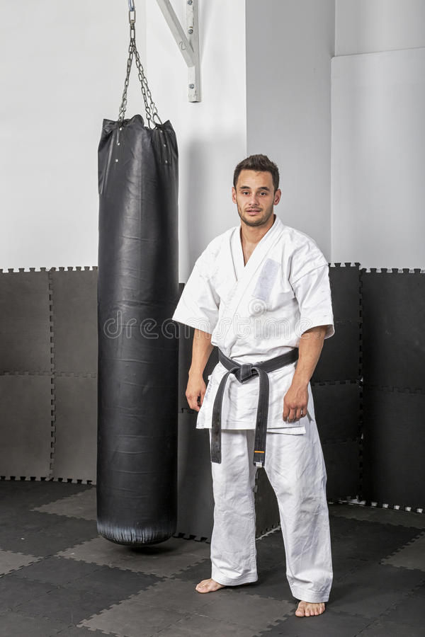 Athletic black belt karate standing next a boxing ba royalty free stock images
