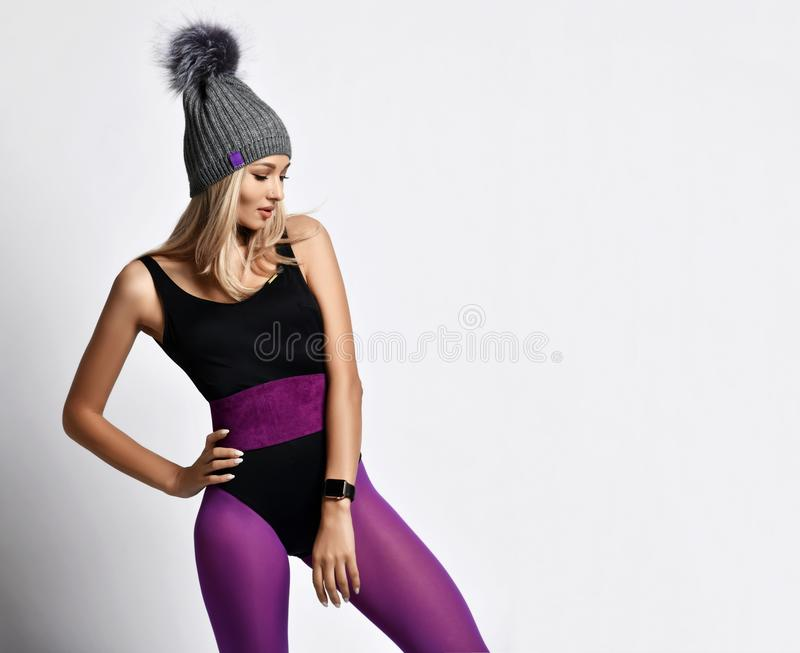 Athletic blonde girl in purple sports wear, gray winter hat and with smart watches standing with one leg to the side. Stylish blonde woman in purple sports wear stock images