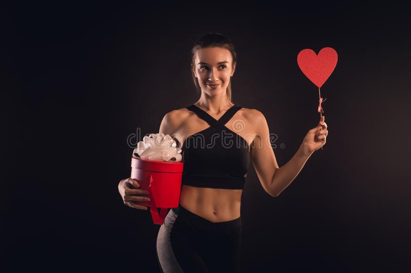Athletic blonde holding a heart and a gift box royalty free stock image