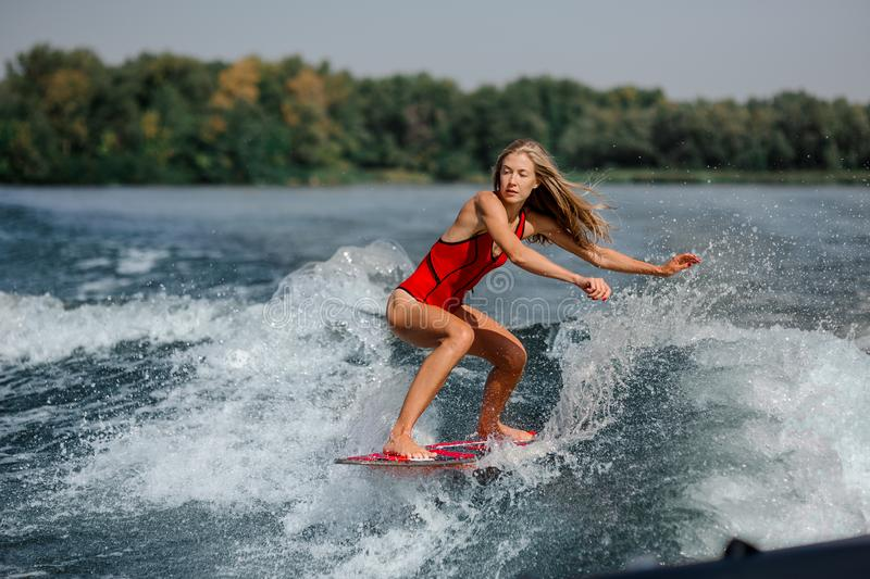 Athletic blonde woman wakesurfing on board down the blue water. Athletic and active blonde woman wakesurfing on board down the blue water on warm day stock images