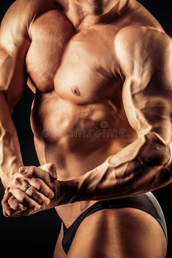 Athletic body. Close-up shot of a handsome muscular bodybuilder posing over black background royalty free stock photo