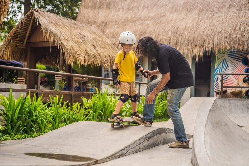 Athletic boy learns to skateboard with asian trainer in a skate park. Children education, sports. Race diversity stock photo