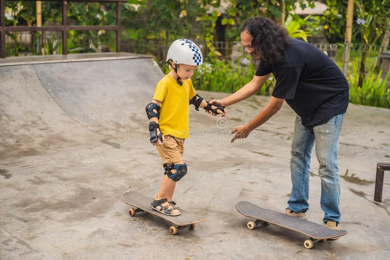 Athletic boy learns to skateboard with a trainer in a skate park. Children education, sports stock photography
