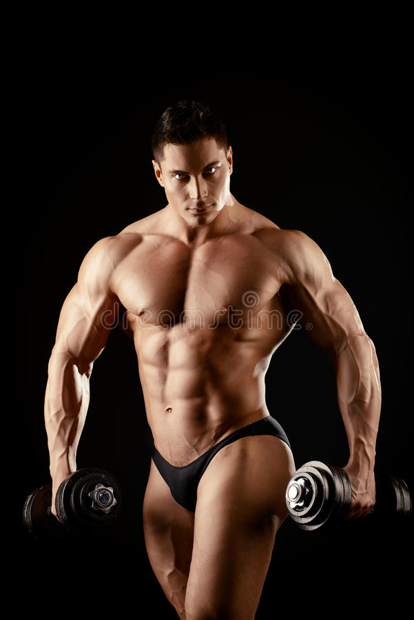 Athletic boy. Portrait of a handsome muscular bodybuilder posing with dumbbells over black background royalty free stock photos