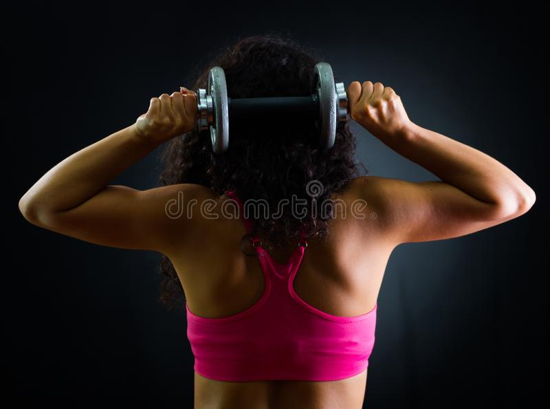 Athletic brunette woman wearing pink top and matching shorts, training lifting weights behind neck, black studio royalty free stock photo