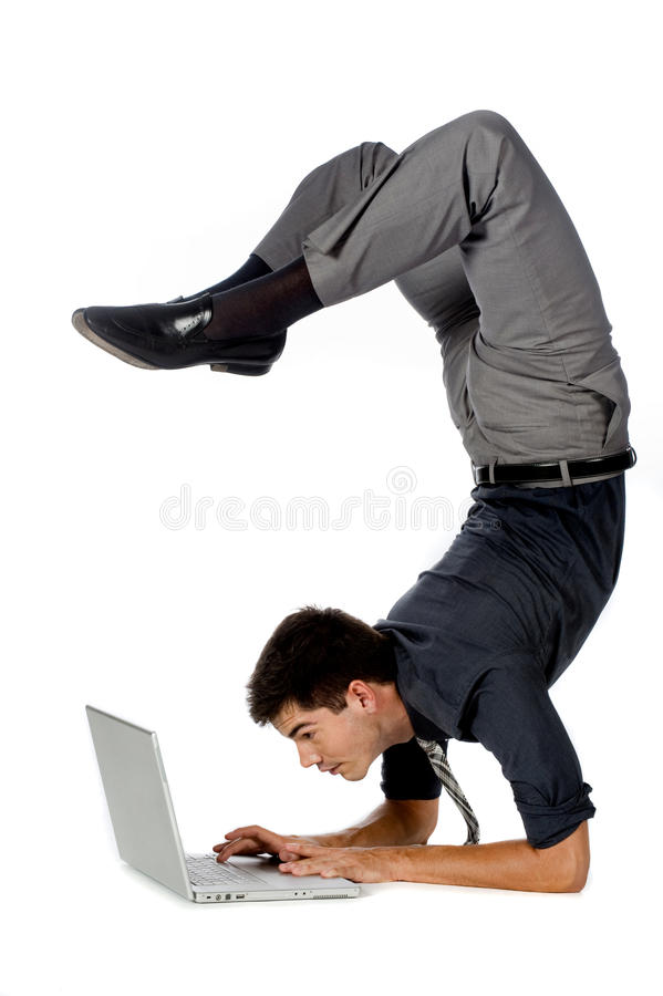Athletic Businessman. An attractive athletic businessman doing a handstand while using his laptop against white background royalty free stock photography