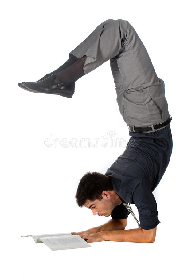 Athletic Businessman. An attractive athletic businessman doing a handstand while reading a book against white background stock photography