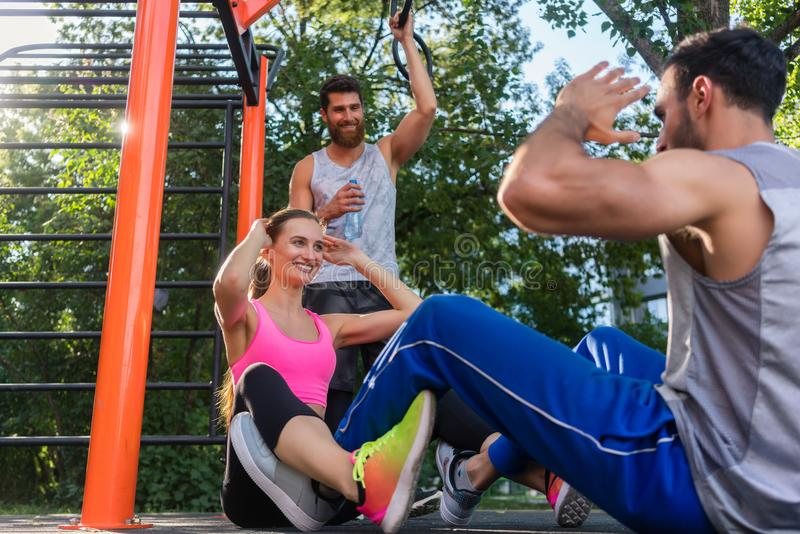 Athletic couple clapping hands while doing crunches face to face. Low-angle view of an athletic couple clapping hands while doing crunches face to face during royalty free stock photo