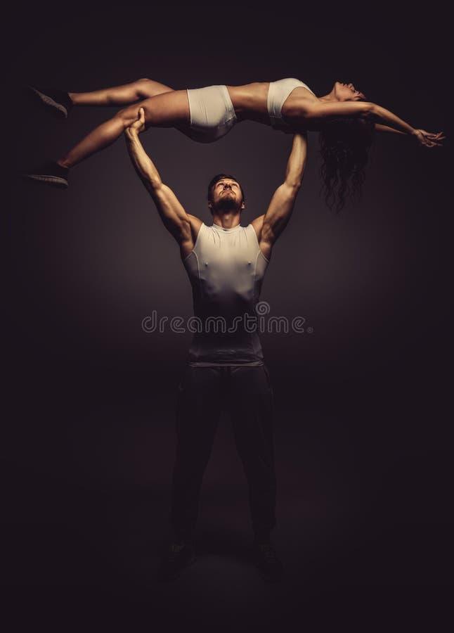 Athletic couple doing acro yoga. Studio shot stock photography