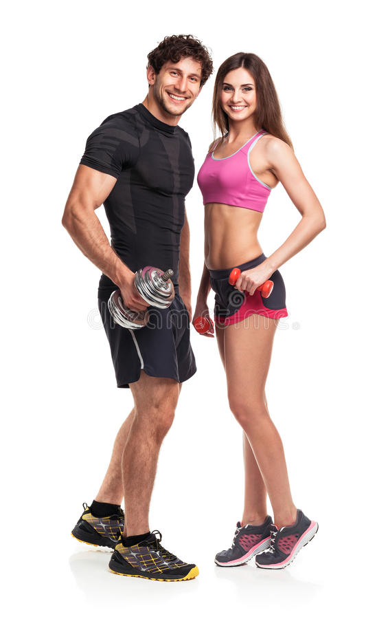Athletic couple - man and woman with dumbbells on the white royalty free stock images