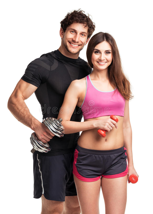Athletic couple - man and woman with dumbbells on the white stock photography