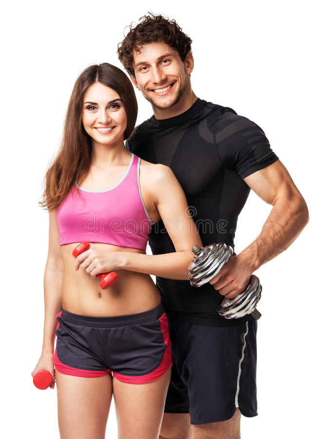 Athletic couple - man and woman with dumbbells on the white stock photo