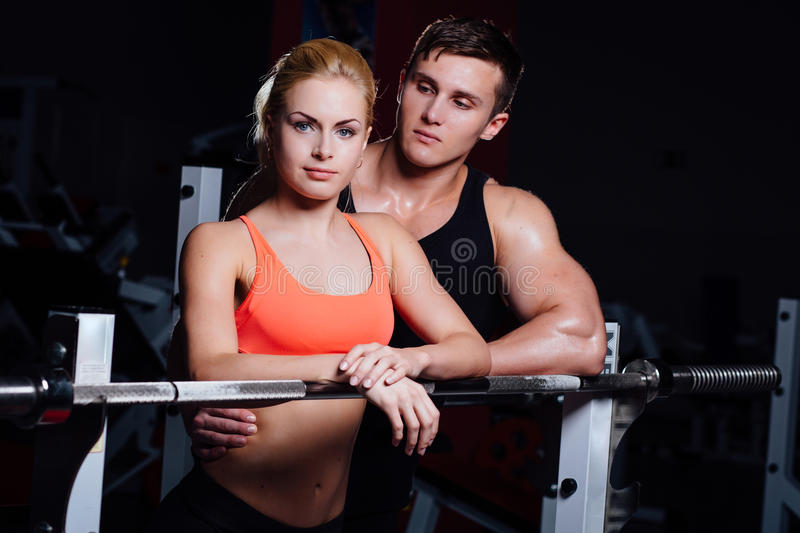 Athletic couple - man and woman Rest between exercises near the barbell in gym royalty free stock image