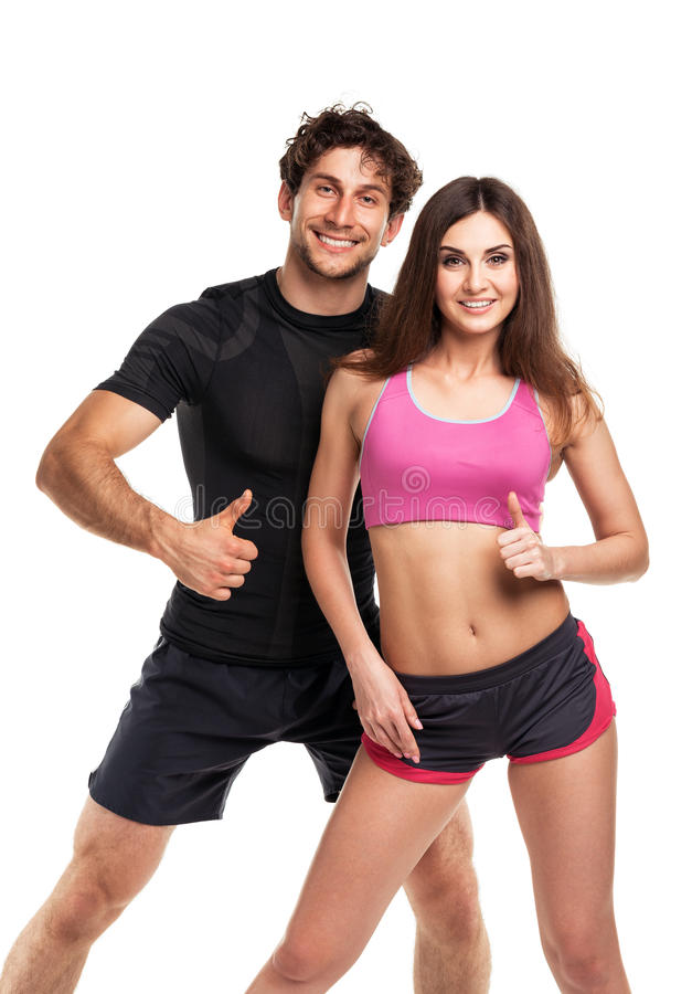 Athletic couple - man and woman with thumb up on the white stock photography