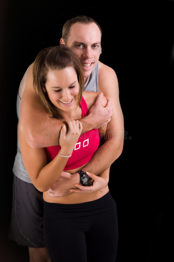 Athletic couple in playful hug stock photography