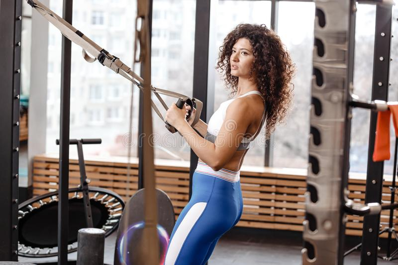 Athletic curly girl dressed in a sportswear has a TRX workout in the modern gym full of sun light royalty free stock photography