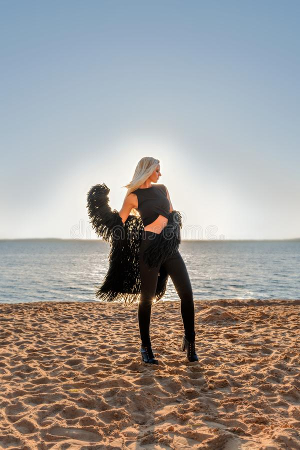 Attractive blond model in black clothes posing in the rays of the rising sun at the seaside. Athletic dancing model in black clothes posing in the rays of the royalty free stock image