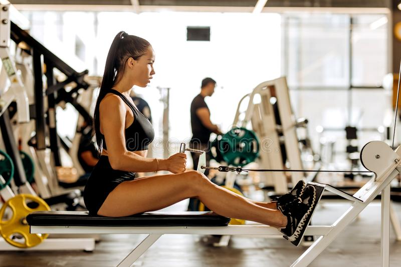 Athletic dark-haired  girl dressed in black sports top and shorts is working out on the exercise machine in the gym stock photography