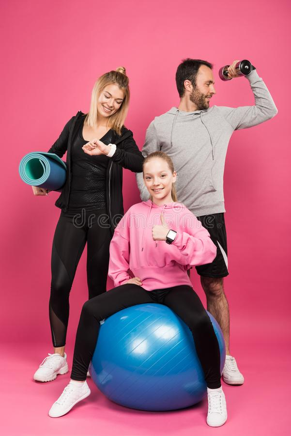 athletic family posing with fit ball, fitness mat and dumbbell while kid showing thumb up, isolated stock image