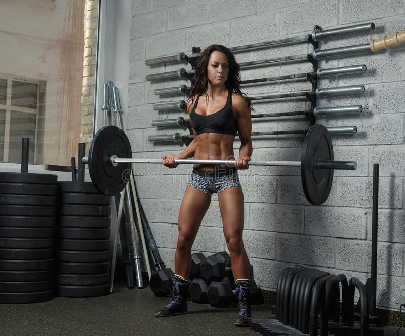 Athletic female holding barbell. royalty free stock images