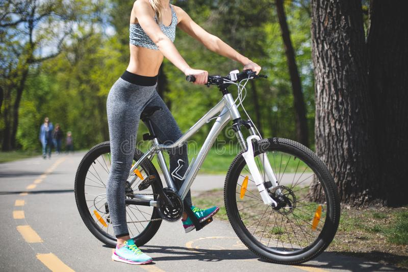 Athletic female is pedaling in park stock images