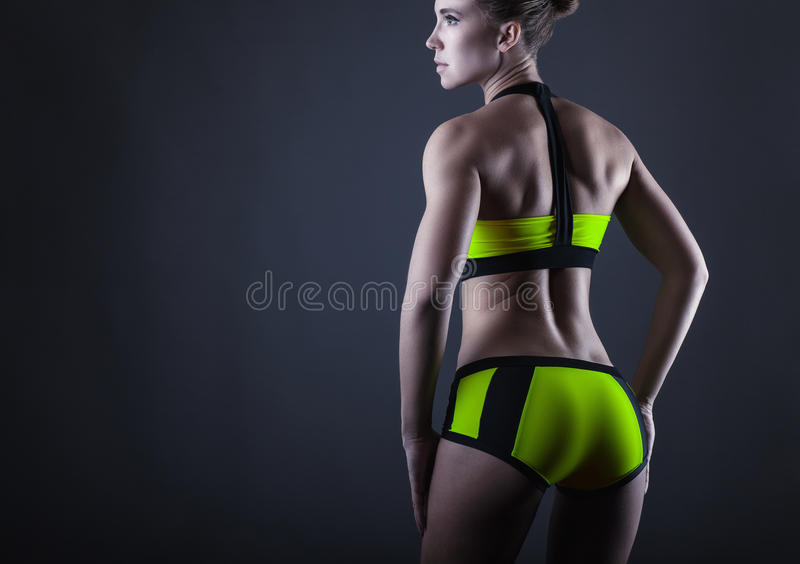 Athletic figure. Young sports woman shows her athletic figure. Back view stock images