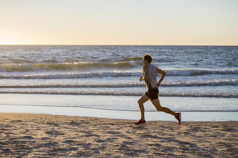 Athletic fit and strong runner man training on Summer sunset beach in sea shore running and fitness workout in sport and healthy l stock images