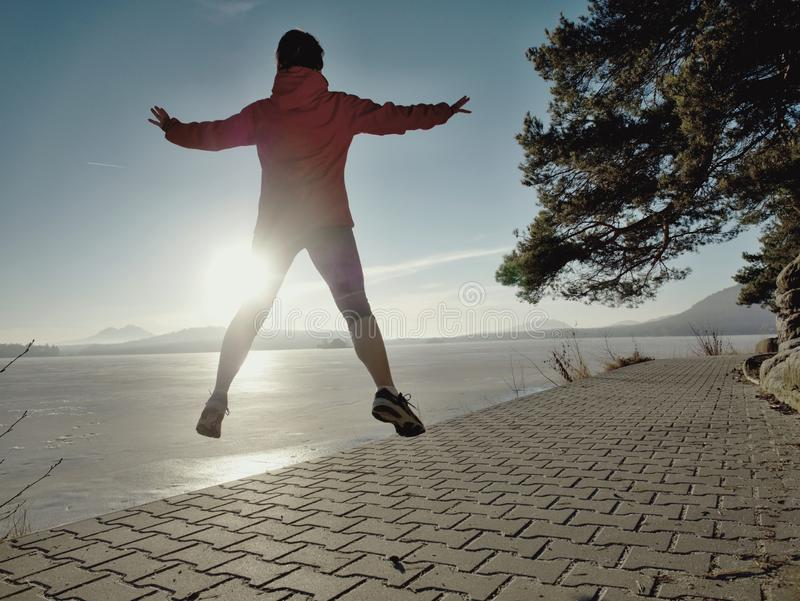 Athletic fitness woman jumping and running on beach at sunset royalty free stock photos