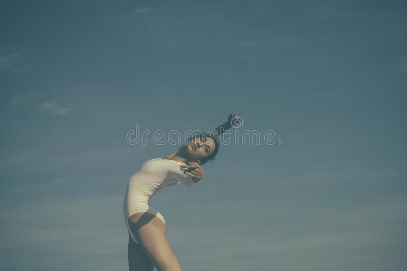 Athletic and flexible. Concert performance dance. Young ballerina dancing on blue sky. Cute ballet dancer. Pretty girl stock image