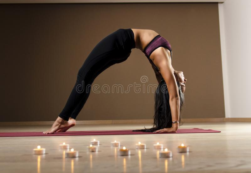 Athletic, flexible yoga woman in wheel pose indoors royalty free stock images