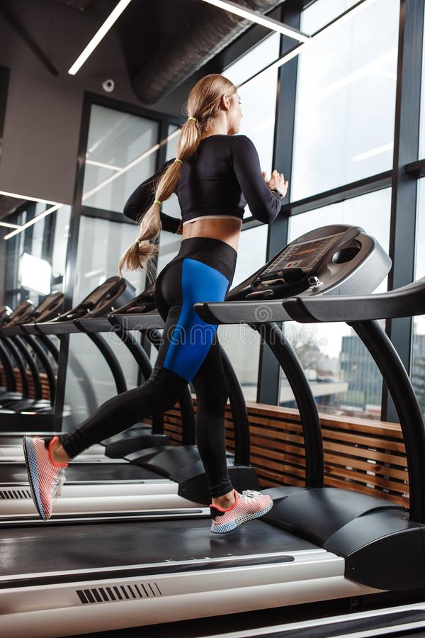 The athletic girl dressed in a sportswear is running on the treadmill in front of the windows in the modern gym.  stock photo