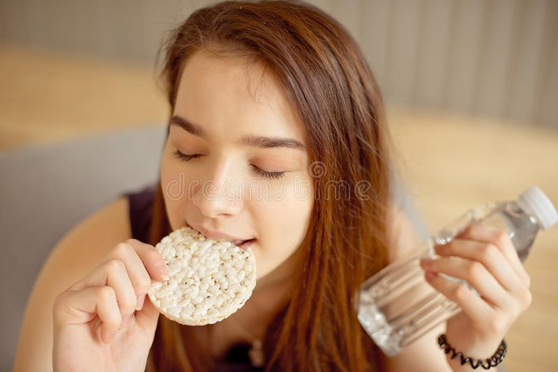Athletic girl eating crunchy rice cakes in her hands holding a bottle of clean water, healthy food, healthy lifestyle. Athletic girl eating crunchy rice cakes stock photography