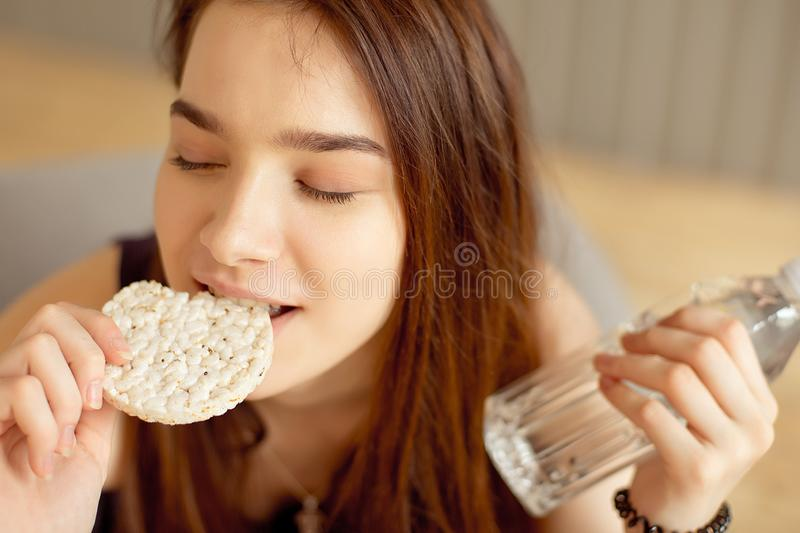 Athletic girl eating crunchy rice cakes in her hands holding a bottle of clean water, healthy food, healthy lifestyle. Athletic girl eating crunchy rice cakes stock photo