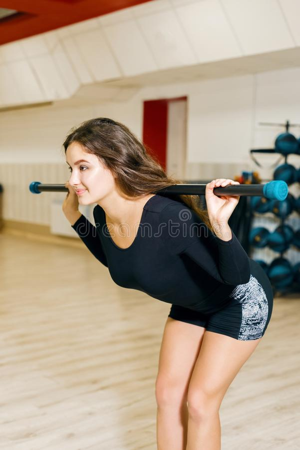 Athletic girl engaged in fitness. woman dealet exercise back bend with a hymastic stick. For aerobics stock photos