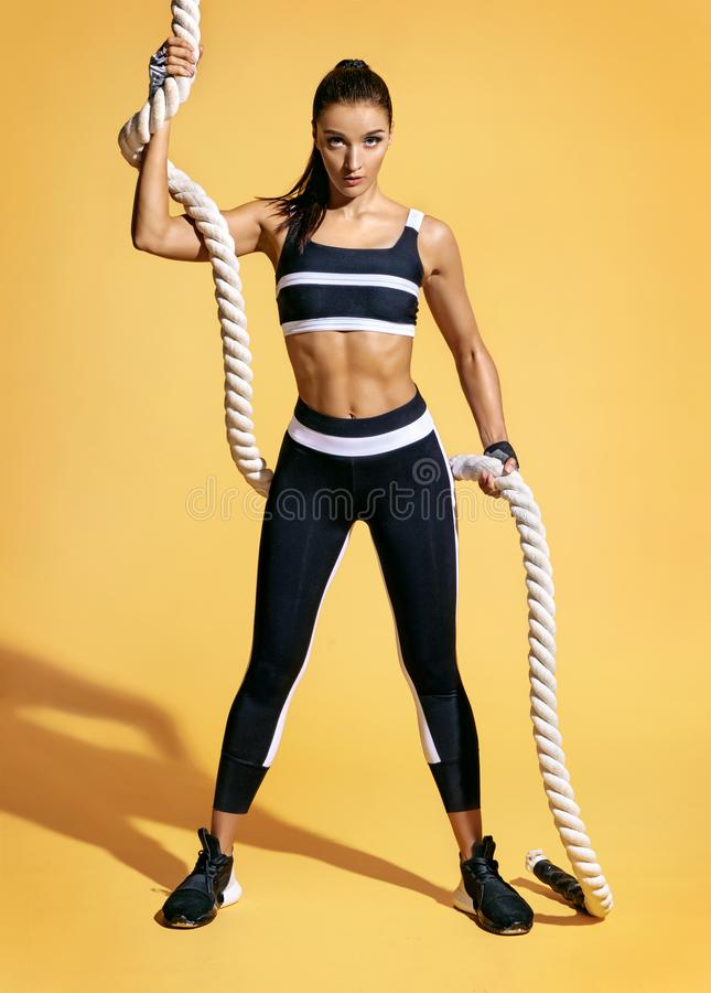 Athletic girl holding heavy ropes and looking at camera. royalty free stock photography