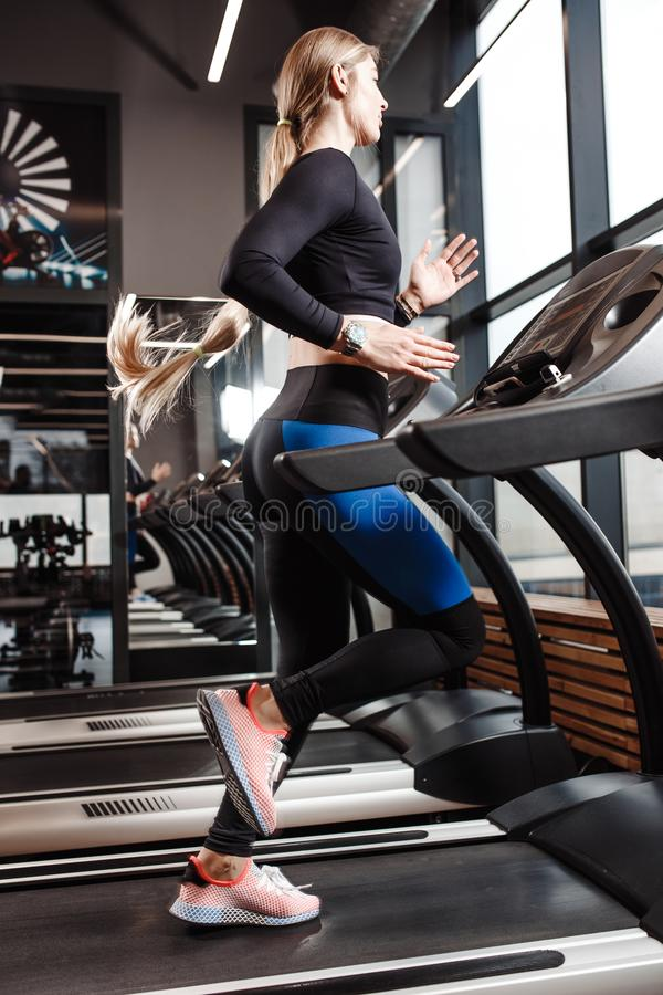 The athletic girl with long blond hair dressed in a sportswear is running on the treadmill in front of the windows in. The modern gym royalty free stock photography