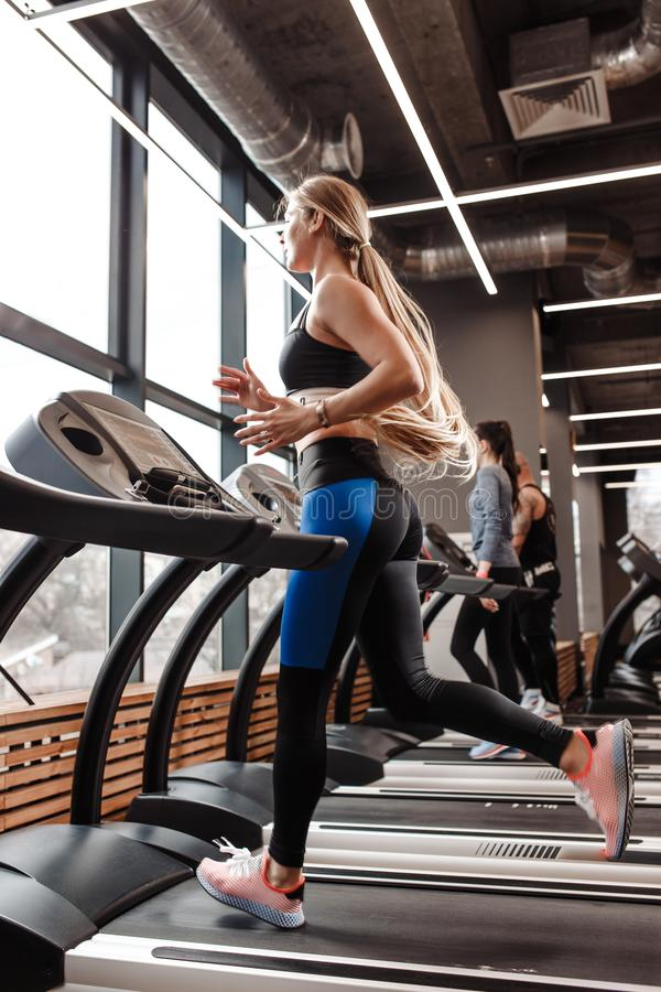 The athletic girl with long blond hair dressed in a sportswear is running on the treadmill in front of the windows in. The modern gym royalty free stock images