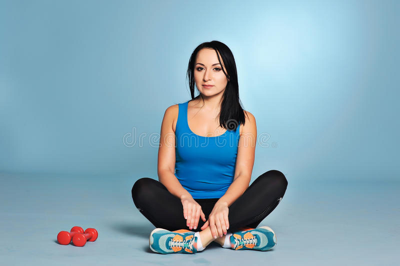 Athletic girl with muscle body sitting on floor stock image