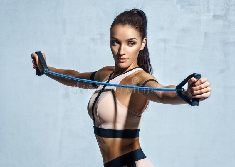 Athletic girl performs exercises using a resistance band. Photo of young girl on drey background. Strength and motivation stock image