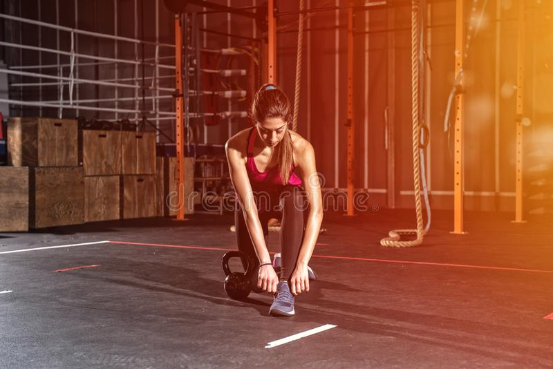 Athletic girl ready to start exercises with a kettlebell at the gym royalty free stock photos