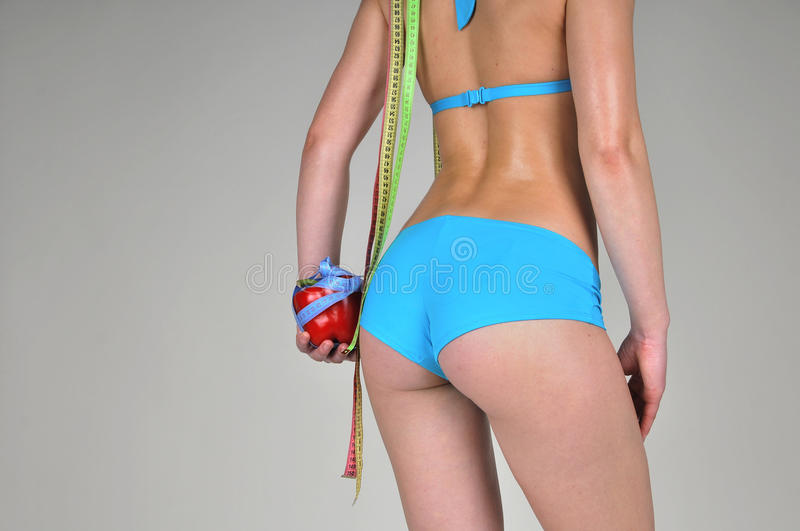 Athletic girl with red pepper and centimeters. royalty free stock photo