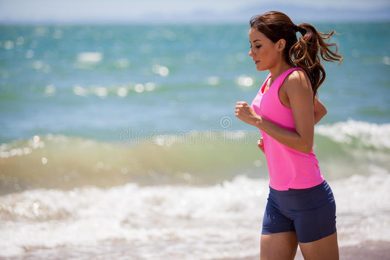 Athletic girl running at the beach. Young athletic woman training and running at the beach stock images