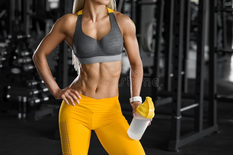 Athletic girl with shaker in gym, drinking water. Fitness woman with flat belly, shaped abdominal, slim waist stock photo