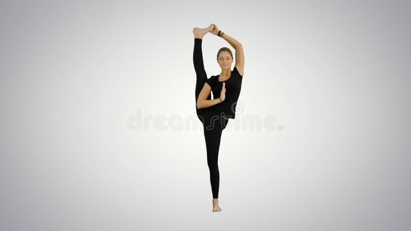 Athletic girl standing in yoga asana utthita hasta Padangustasana, extended hand to big toe yoga pose stretched hand stock photo