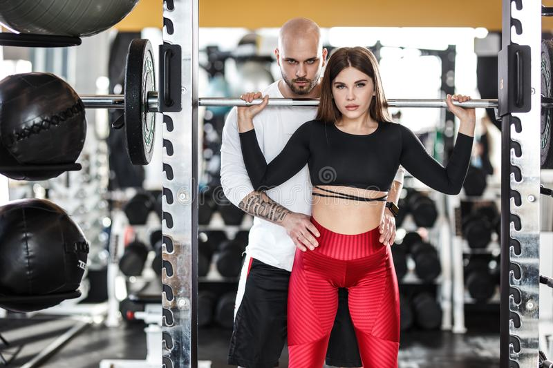 Athletic girl in stylish bright sports clothes doing back squats and strong athletic man helps her in the modern gym royalty free stock images