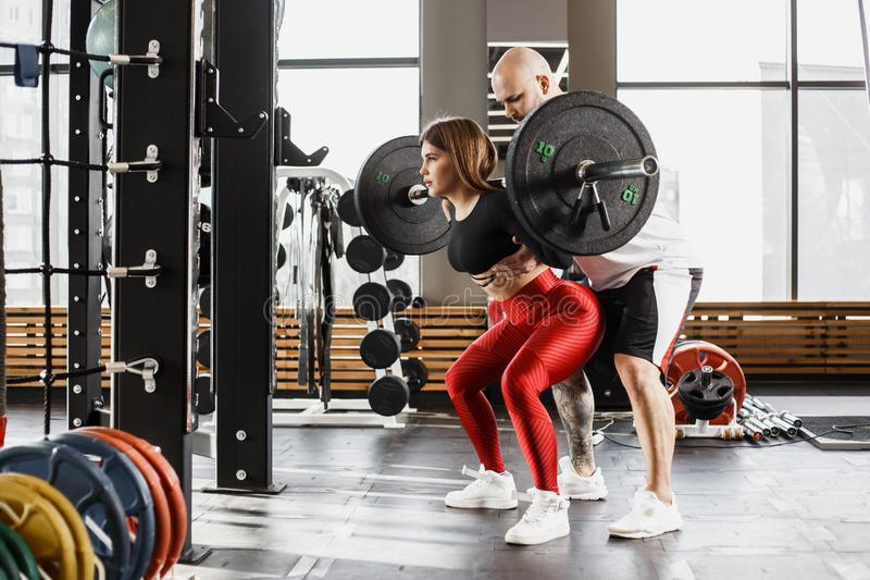 Athletic girl in stylish bright sports clothes doing back squats and strong athletic man helps her in the modern gym stock photography