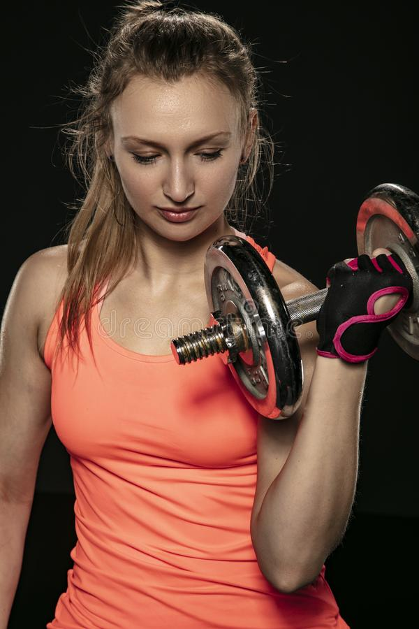 An athletic girl trains with barbells royalty free stock photo